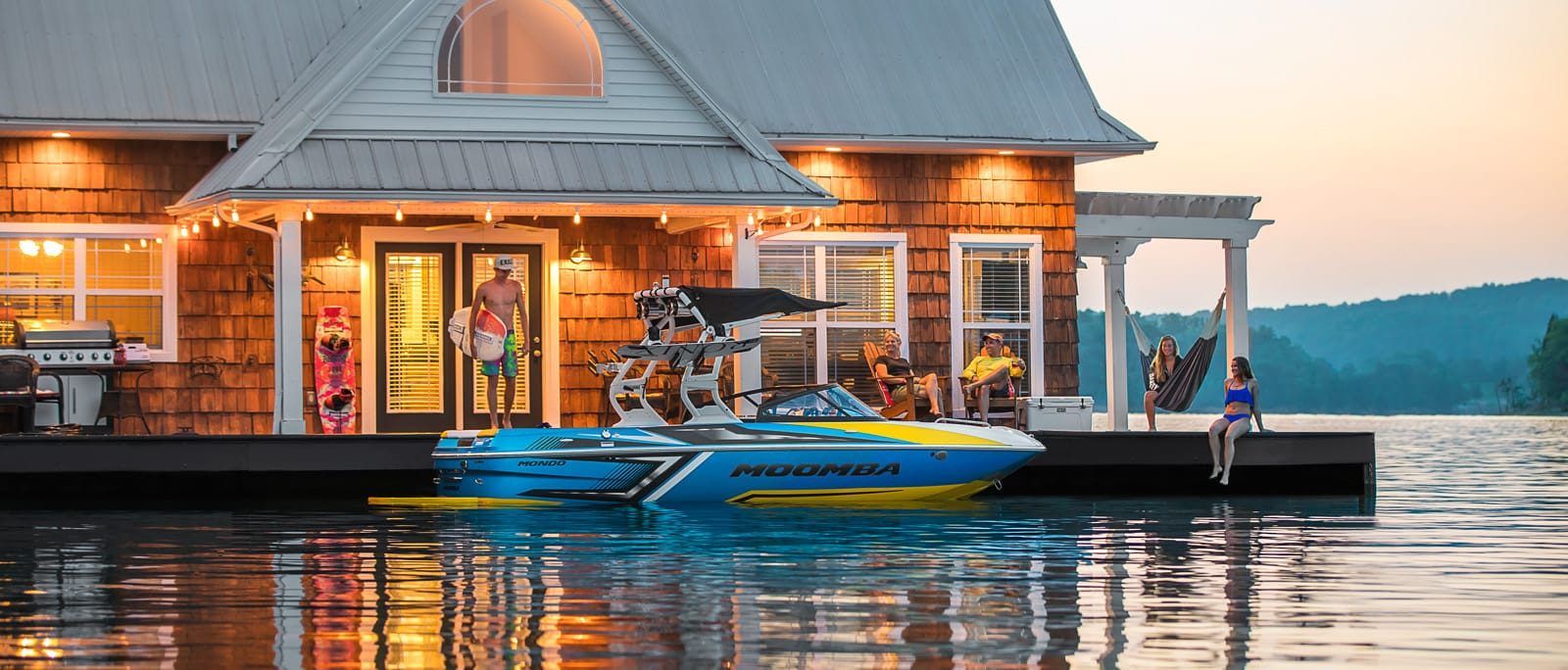 A family gets onto a Mailibu wakeboard boat on a boat dock