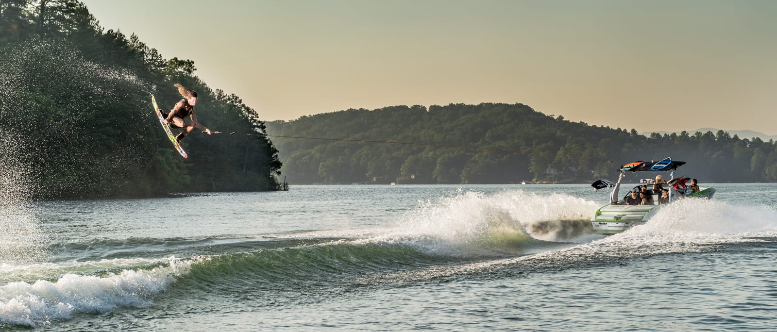 A wakeboarder catches a wave out on the water