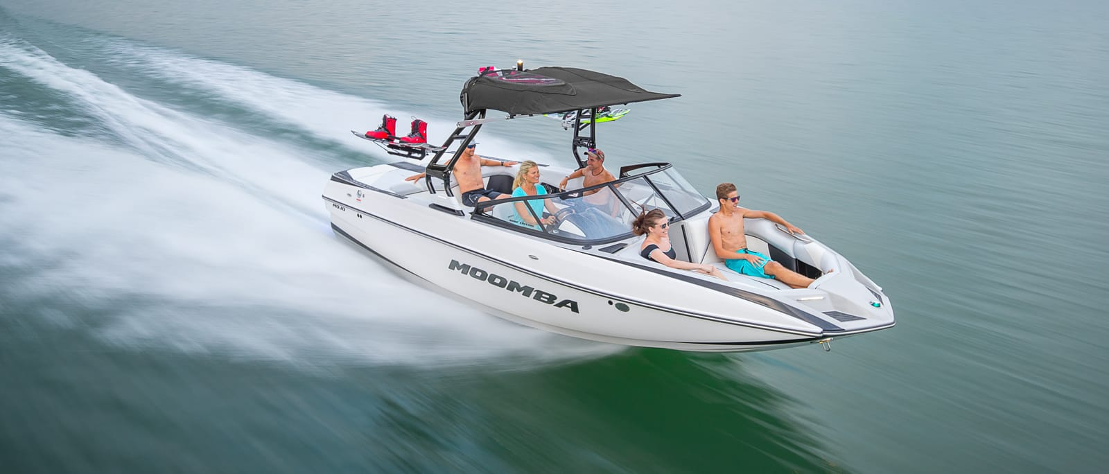 A family enjoying a Moomba wakeboard boat on the water