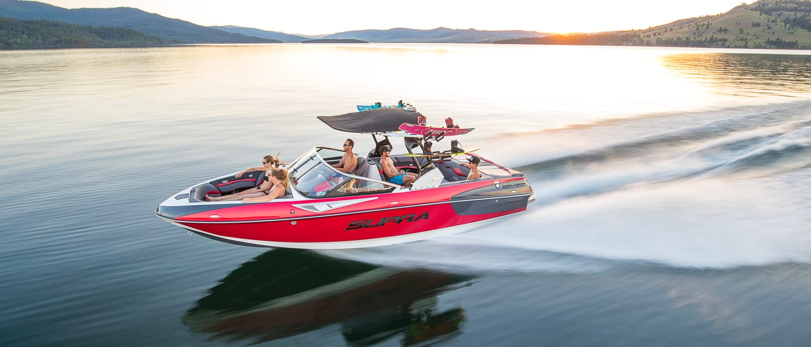 A group of people on a Supra wakeboard boat on the water