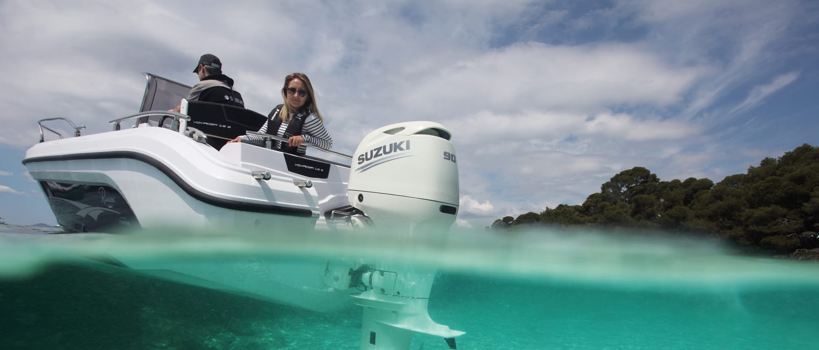 A Suzuki outboard motor on a boat in the water